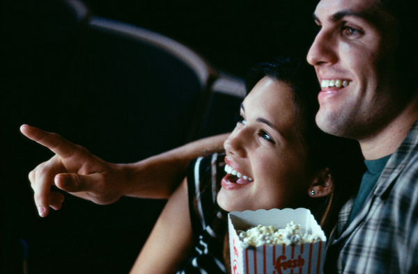 Close-up of a young couple watching a movie in a t